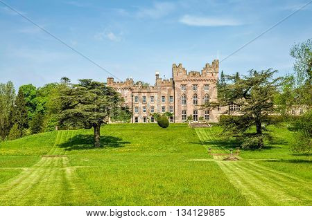 Green grounds of Hutton in the Forest country estate in Skelton, Cumbria, England against blue skies on sunny day.