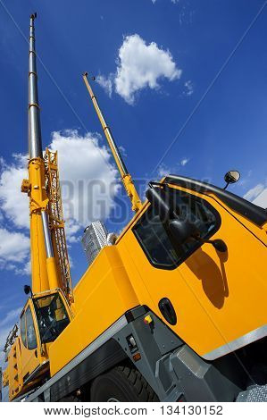 Mobile construction cranes with telescopic arms mounted on trucks with yellow bodyworks in sunny day with white clouds and deep blue sky on background, heavy industry