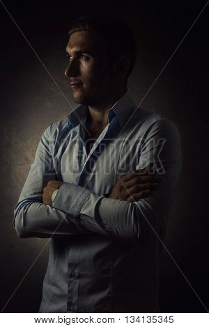 young optimistic businessman with folded arms looking sideways in front of grunge background