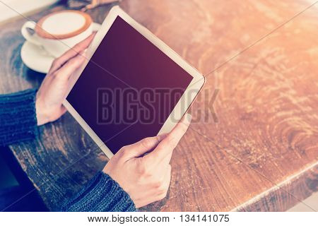 Asian Woman Hand Holding Tablet And Using Tablet In Coffee Shop With Vintage Toned.