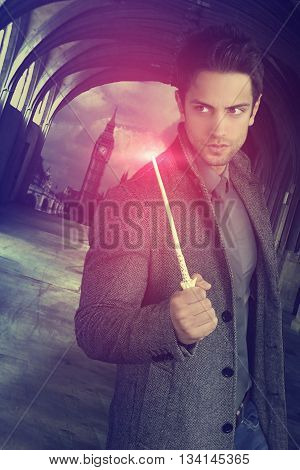 Handsome young wizard holding a magic wand