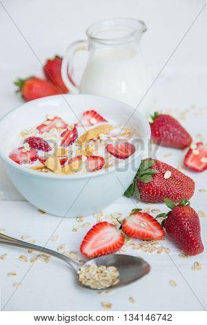 Porridge with fresh strawberry and milk on white