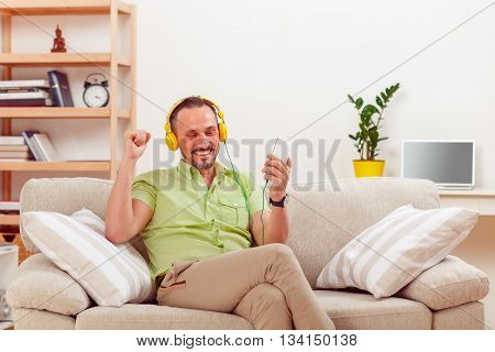 Portrait of handsome man looking at his mobile or smart phone while listening to music at home. Happy man sitting on sofa or couch.