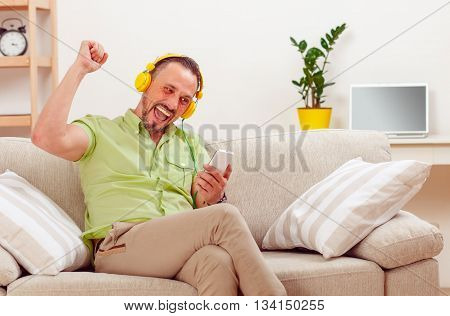 Portrait of handsome man happy smiling or laughing while spending his free time at home listening to music.