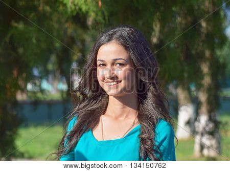 Girl with toothy smile and brown hair in a green dress. The beautiful young girl.