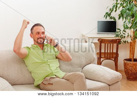 Portrait of handsome man smiling while speaking over mobile or smart phone. Happy man sitting on sofa or couch and looking to camera.