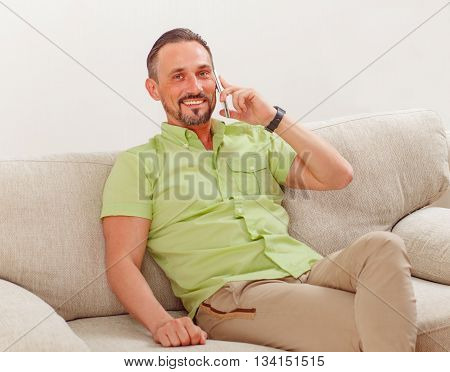 Portrait of handsome man smiling while speaking over mobile or smart phone. Happy man looking at camera at home.