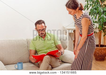 Portrait of handsome man looking at documents while his wife standing near him. Businessman preparing for meeting from home.