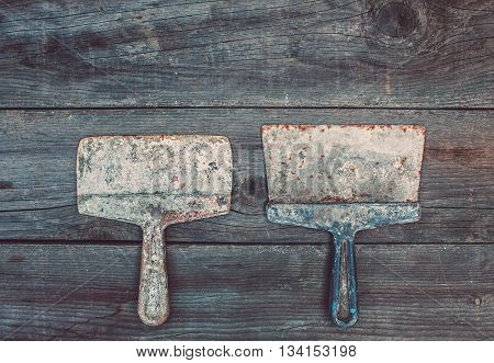 On the old wooden cracked the working surface in the studio are two vintage used rusty darkened mettalic smeared with mortar instruments of different sizes - spatulas. Close-up.