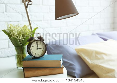 Lamp, books and alarm clock on a side table