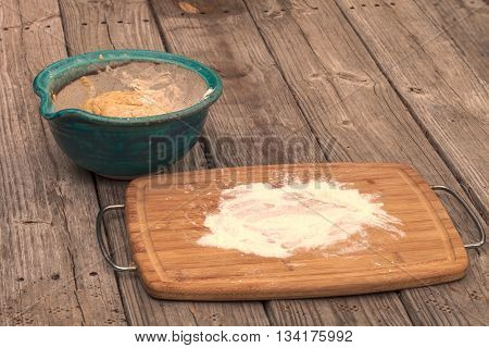 Number 9 of bread making series.  Bread dough rises in a bowl with a cutting board spread with flour on a rustic picnic table.