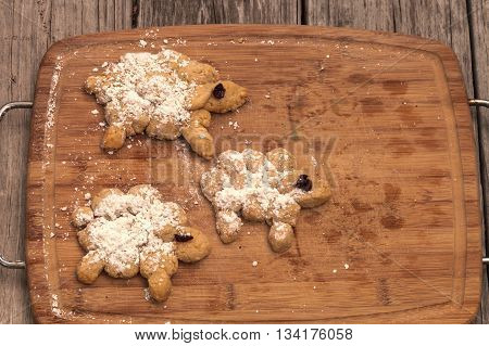 Number 12 of bread making series.  Bread sheep with powdered sugar and dried cherry eyes on a wood cutting boarad.