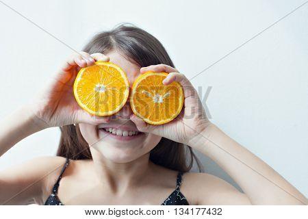 Little girl holding two halves of orange instead of glasses