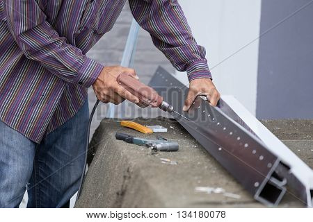 Worker Drilling Holes In Aluminium Construction Frame With Electric Drill