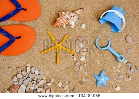 high-angle shot of some summer stuff, such a pair of flip-flops, a conch, a starfish, some pebbles and seashells or a small beach pail and a toy shovel, on the sand of a beach