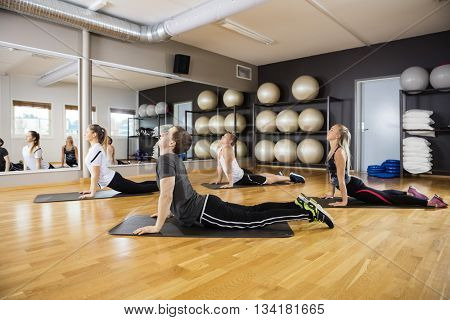 Friends Performing Upward Dog Pose In Gym