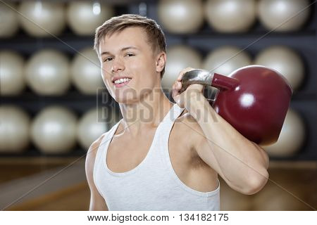 Attractive Man Exercising With Kettlebell In Gymnasium