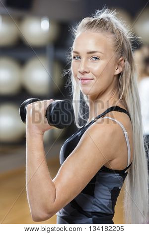 Confident Young Woman Lifting Dumbbell In Gym