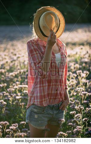 Farmer woman hiding behind panama hat. Country girl using hat.
