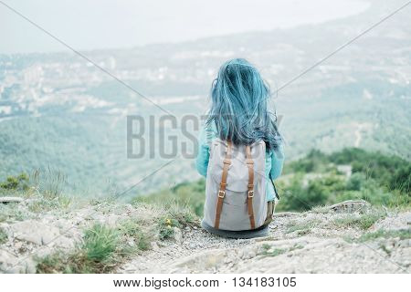 Traveler young woman with backpack resting on peak of mountain rear view