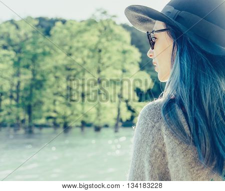 Beautiful young woman with blue hair wearing in hat and glasses resting on lake in summer