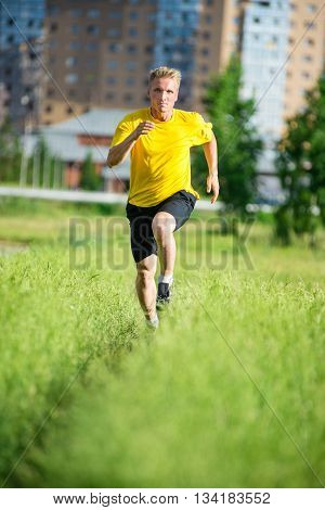 Running man jogging in city street park at beautiful summer day. Sport fitness model caucasian ethnicity training outdoor.