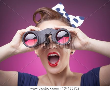 Pin Up girl loking through binoculars on pink background