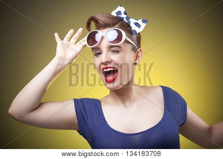 Portrait of a beautiful Pin Up girl holding the sunglasses on yellow background