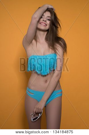 sexy cute smiling brunette woman wearing blue bikini on orange