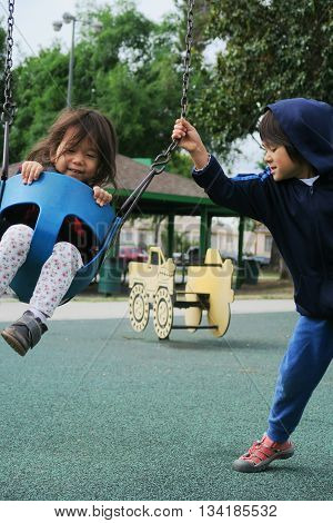 Brother and sister having a lot of fun together with the swing