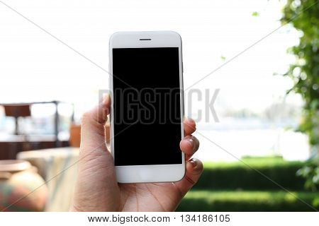 Hand holding smartphone with green garden background