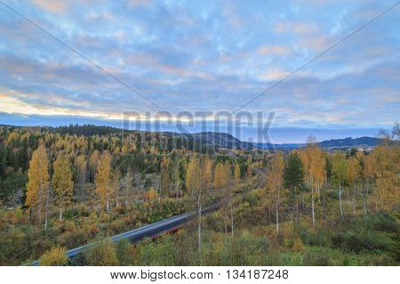 train with trees and mountains in autumn during sundown