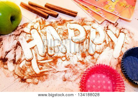 word happy written on a white table with cinnamon