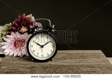 Alarm clock on wood with Black color in background. Time of Remembrance Concept.
