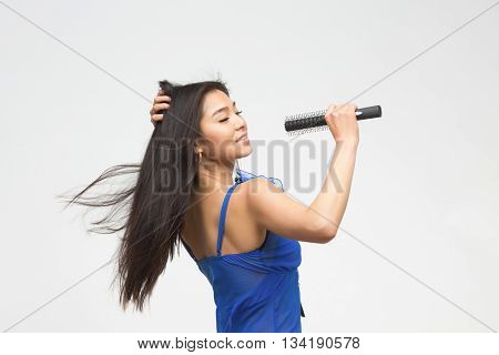 Portrait of singing fashion asian model in blue lingerie or underwear in studio. Beautiful woman with black hair holding microphone in front of her.