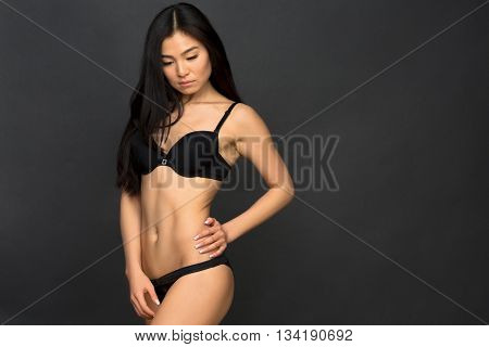 Attractive asian sexy fashion model with natural hair, full lips, perfect skin posing in studio. Beautiful lady wearing black underwear. Beauty photo shot, retouched image.