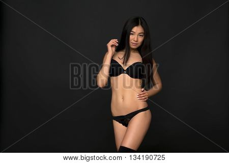 Picture of fashion asian model in lingerie posing infull length in studio. Gorgeous lady keeping one hand on hip over grey background.