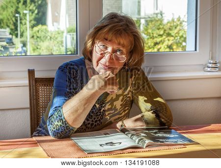 Elderly Attractive Woman Reading In A Magazine