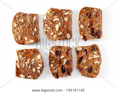 multigrain bread slices with fruits and nuts close-up on white background