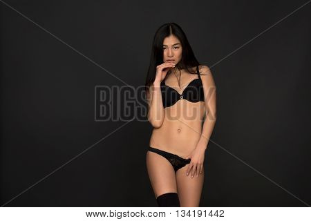 Portrait of beautiful fashion asian model in black lingerie or underwear looking at camera in studio. Brunette lady posing for fashion magazine.