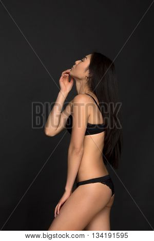 Profile of brunette lady looking upwards over grey background. Gorgeous fashion asian model in black lingerie or underwear in studio.