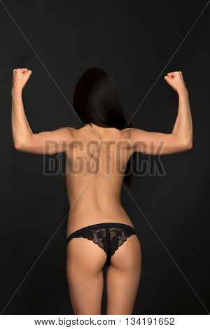 Topless fashion asian model posing in black lingerie or underwear in studio. Brunette lady showing her muscles.