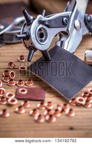 Metal handheld revolving plier and rivets on wooden background
