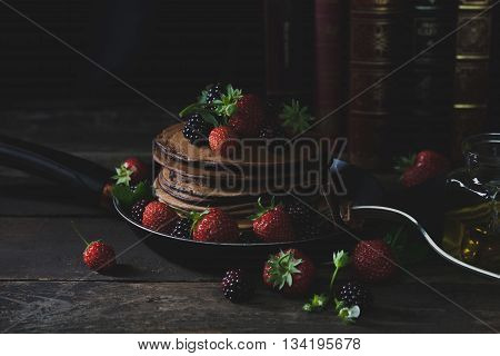 Pancakes in the rusty pan with strawberries and blackberries honeyfork and old books in background with mystical light