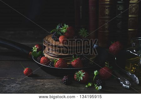 Pancakes in the rusty pan with strawberries honey and old books in backgound with mystical light