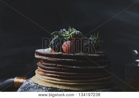 Chocolate pancakes in rusty pan with organic fruits like strawberries and blackberries with honey