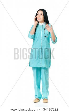 Full length portrait of a young beautiful doctor with phone against white background.