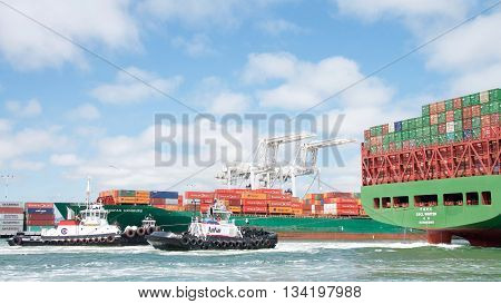 Oakland CA - June 09 2016: Tugboats SANDRA HUGH and REVOLUTION at the stern of Cargo Ship CSCL WINTER assisting the vessel to maneuver into the Port of Oakland.