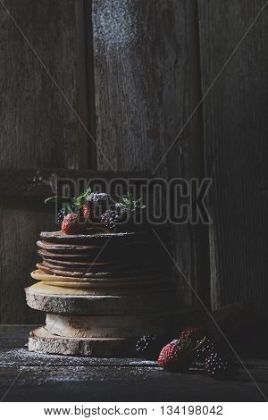 Chocolate pancakes with organic fruits on wooden blocks with old wooden doors in backround