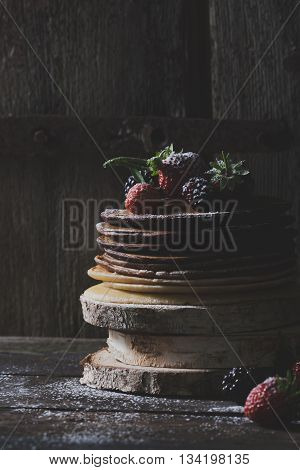 Rustic chocolate pancakes with organic fruits like strawberries and blackberries on wooden blocks with old wooden doors in backround